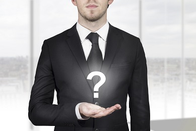 businessman in black suit holding white question mark in open hand
